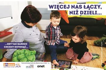 Chłopiec i dziewczynka wspólnie bawią się tabletem. Chłopiec, który nie ma rąk obsługuje urządzenie stopą. Przed nimi napis: Więcej nas łączy, niż dzieli