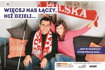Aktorka Agnieszka Więdłocha i niewidomy mężczyzna kibicują polskiej reprezentacji siedząc przed telewizorem. Przed nimi napis: Więcej nas łączy, niż dzieli