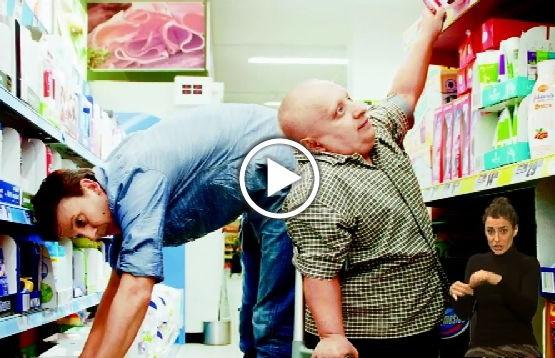 Dwóch mężczyzn przy sklepowych półkach. Wysoki mężczyzna nie może sięgnąć produktów z dolnych półek, a niskorosły z górnych. Plakat kampanii Więcej nas łączy, niż dzieli
