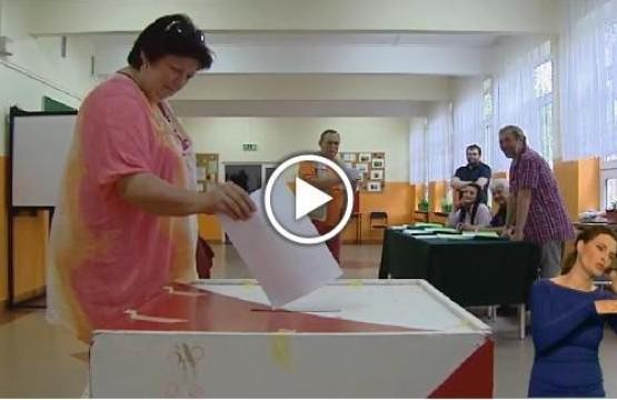 Kobieta wrzuca kartę do głosowania do urny wyborczej