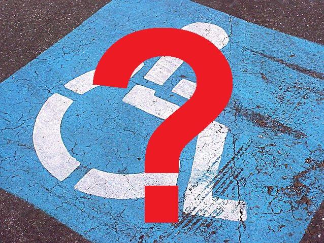 Namalowany na jezdni symbol osoby na wózku na niebieskim tle. Zdjęcie przykrywa znak zapytania