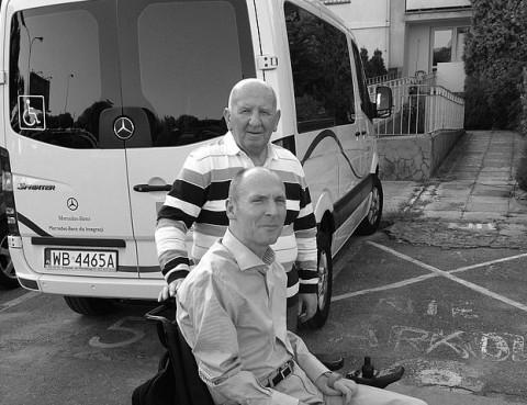Czarno-białe zdjęcie Macieja Pawłowskiego, stojącego nad synem, Piotrem, siedzącym na wózku