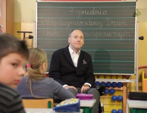 Piotr Pawłowski w klasie, przed nim siedzą dzieci, za nim znajduje się tablica z napisem: 3 grudnia, Międzynarodowy Dzień Osób Niepełnosprawnych