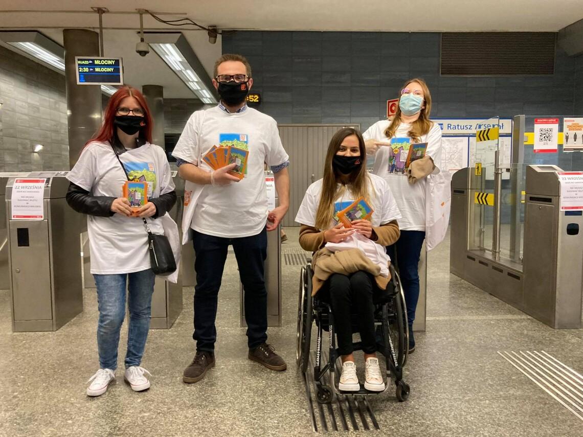 Grupa osób (4) w koszulkach integracji stoi przed bramkami metra. Wszyscy trzymają w dłoniach broszurę Integracji Savoir vivre.
