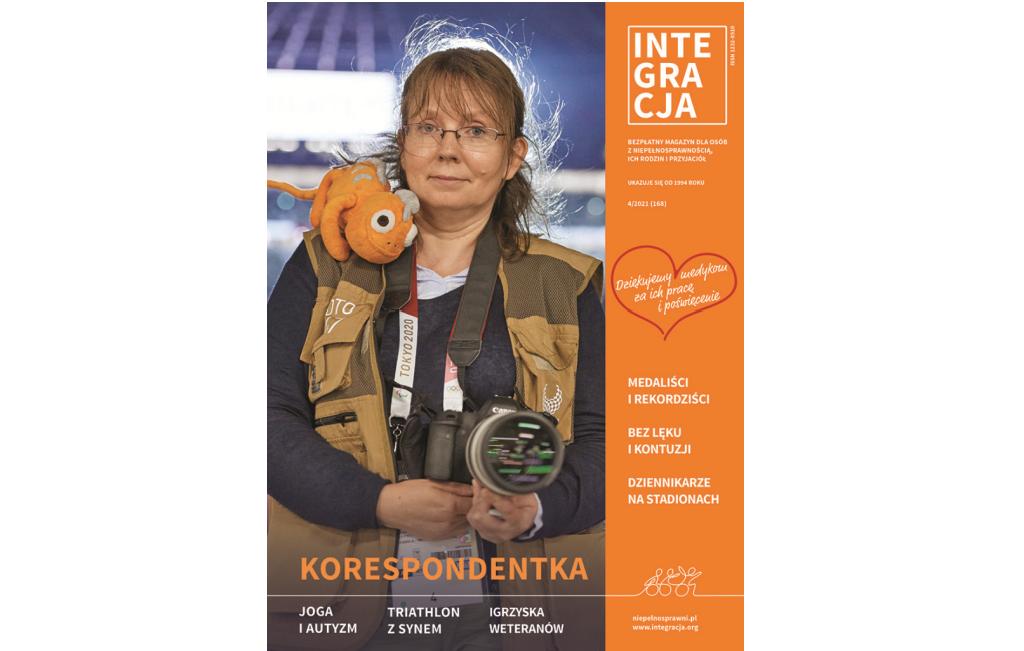 Okładka magazynu Integracji nr 4/2021. Na okładce Ilona Berezowska patrzy prosto w obiektyw, ma okulary, jest ubrana w kamizelkę korespondentki z Tokio, trzyma aparat w dłoniach, ma maskotkę na ramieniu